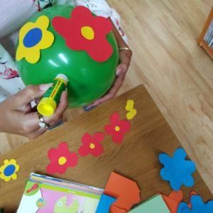 Przyklej Kolorowe Kwiaty Do Balonu. Możesz Użyć Kleju, Ale Najlepiej Trzymają Się Na Taśmie Dwustronnej